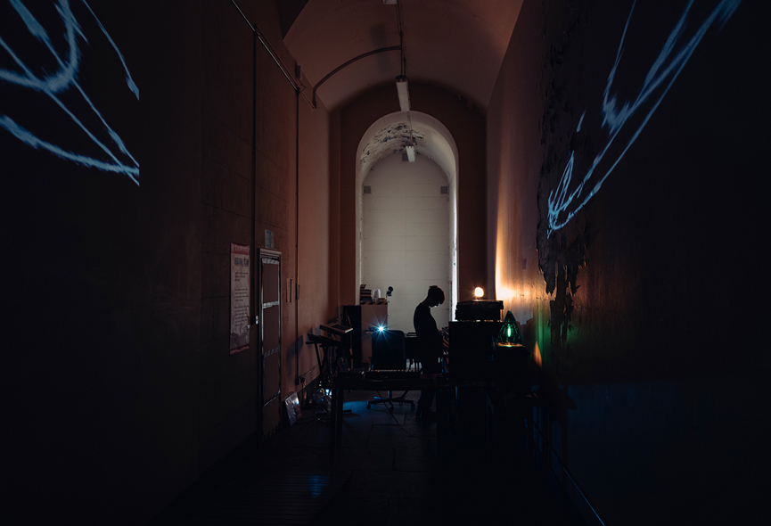 Photograph of a woman DJing in a dark archway